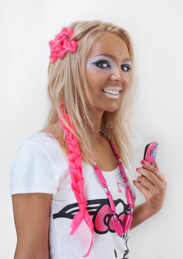 Smiling ganguro style girl with cell phone royalty free stock photo