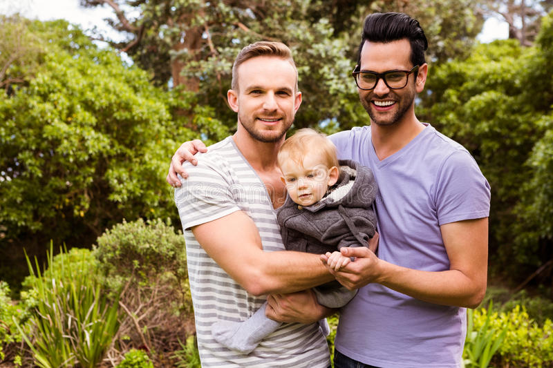 Smiling gay couple with child stock photography