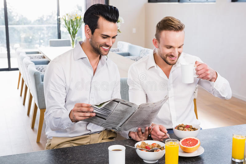 Smiling gay couple reading newspaper royalty free stock photos