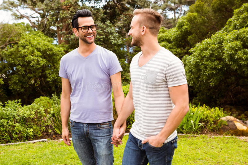 Smiling gay couple walking hand in hand stock photo