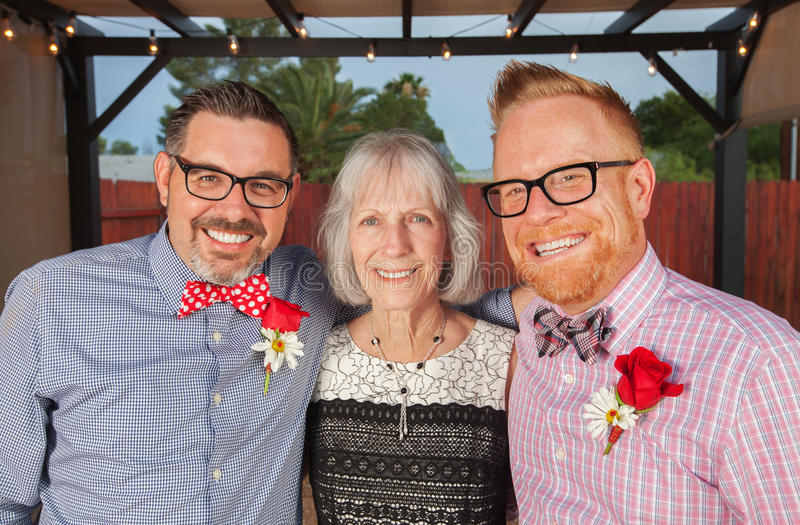 Smiling Gay Men with Mother. Gay spouse with mother and partner in outdoor wedding royalty free stock images
