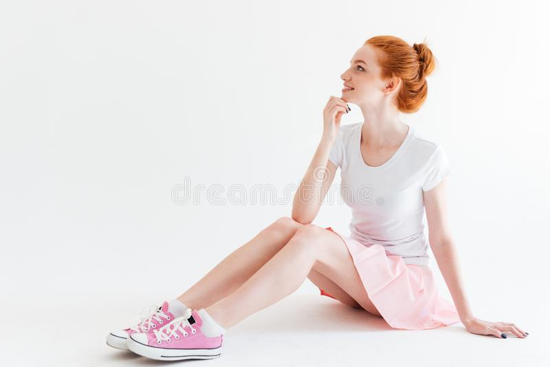 Smiling ginger girl sitting on the floor and looking away. Over white background royalty free stock images