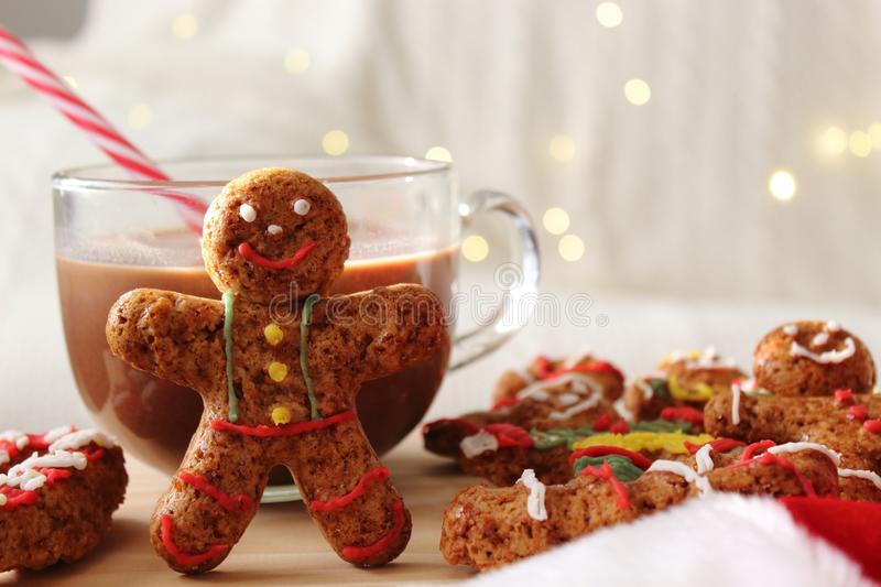 Smiling gingerbread man standing next to chocolate mug. Table of additional cookies. Smiling gingerbread man standing next to chocolate mug. Table of additional stock image