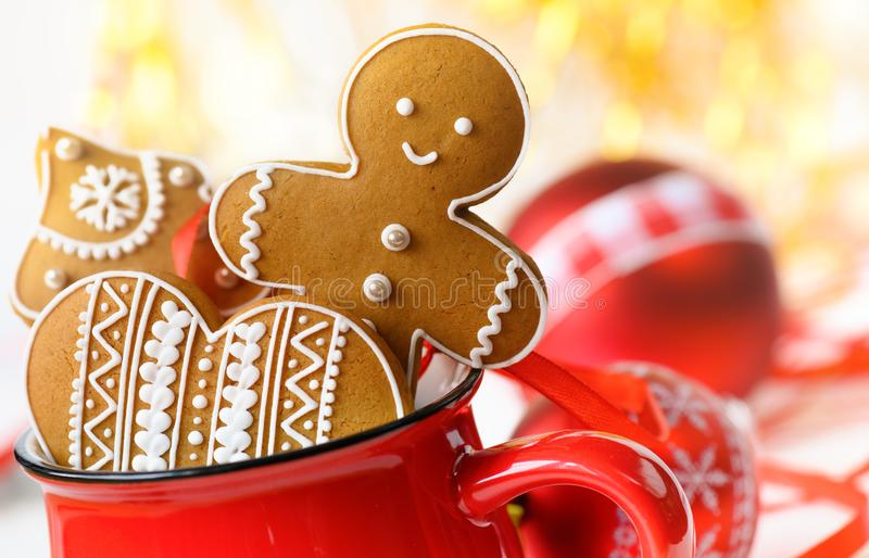 Gingerbread cookie men in a red cup. Smiling Gingerbread men and christmas cookies in a red cup on christmas baubles background royalty free stock photo