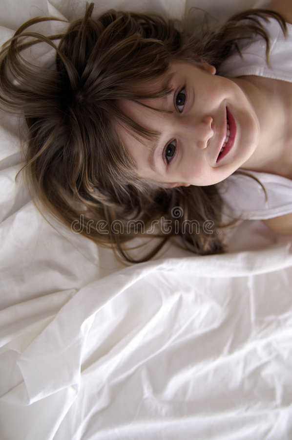 Smiling girl. A young girl playing in the sheets stock photo