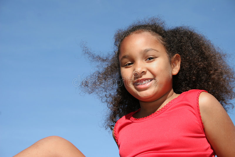 Smiling girl. Low angle view of smiling multiracial girl with blue sky background stock images