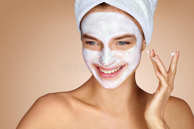 Smiling girl applying cosmetic facial mask stock photos