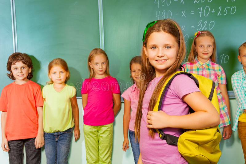Smiling girl with bag and other pupils behind stock photo