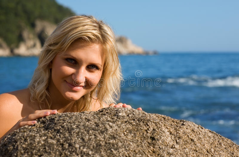 Smiling girl on the beach. By the sea royalty free stock photography
