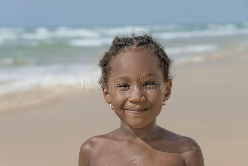 Smiling girl at the beach, six years old royalty free stock photos