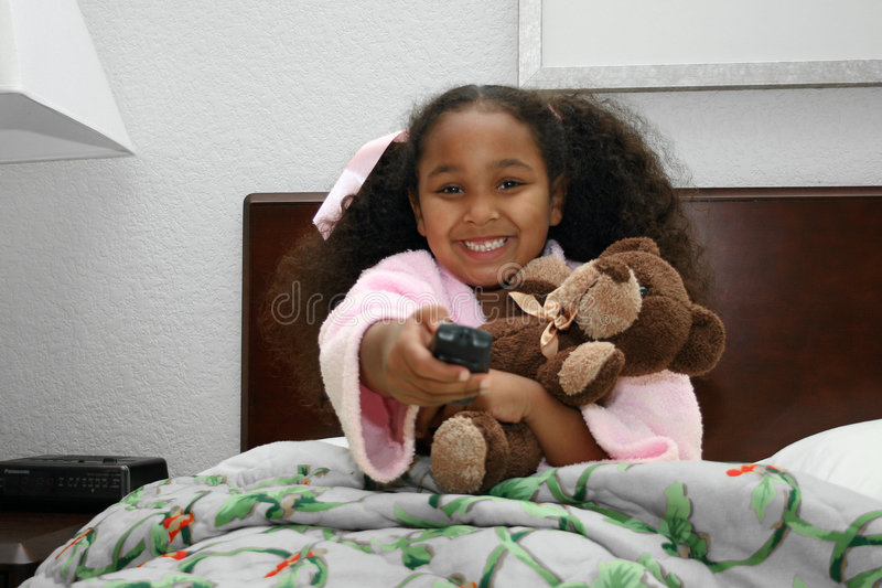 Smiling girl in bed. Close up of smiling multiracial girl cuddling teddy bear in bed. She is pointing a remote control device royalty free stock photos