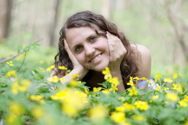 Smiling girl with big bouquet of spring flowers lying. On green grass. Mothers day concept royalty free stock photography