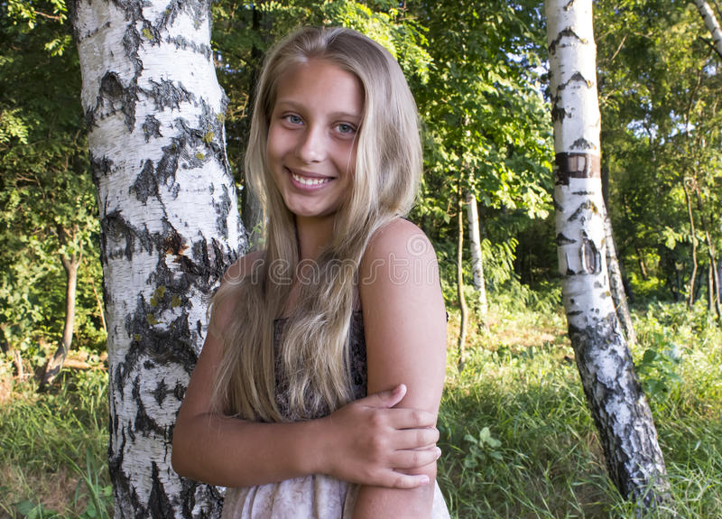 Smiling girl among the birches at sunrise stock photography