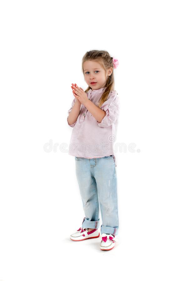 The girl the blonde in a shirt and jeans on wite background. The smiling girl the blonde in a shirt and jeans stands and claps in palms royalty free stock image