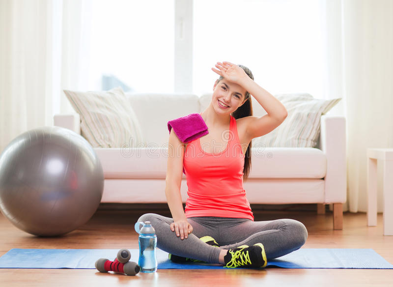 Smiling girl with bottle of water after exercising stock image