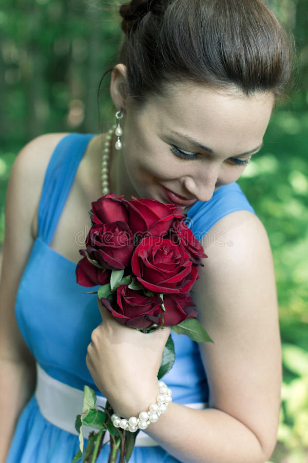 Smiling girl with bouquet of red roses royalty free stock image