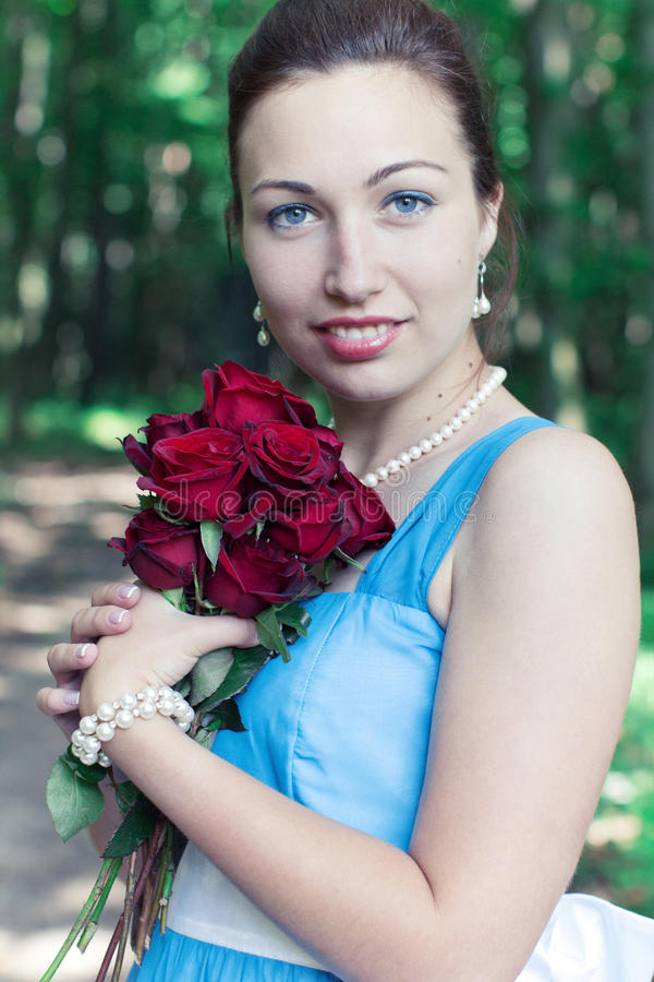 Smiling girl with bouquet of red roses royalty free stock photos