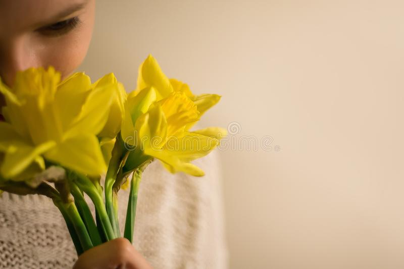 A smiling girl with a bouquet of yellow spring flowers, narcissus stock photos