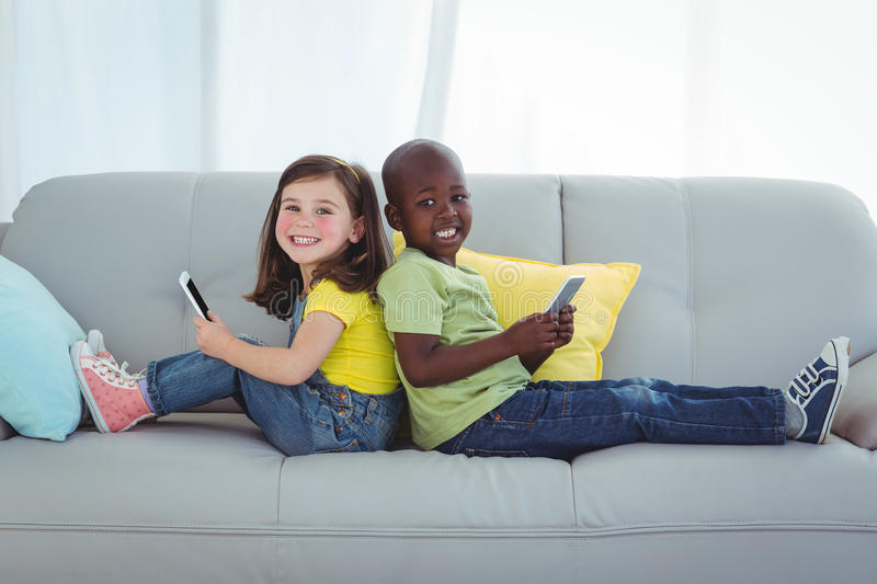 Smiling girl and boy using mobile phones stock photography