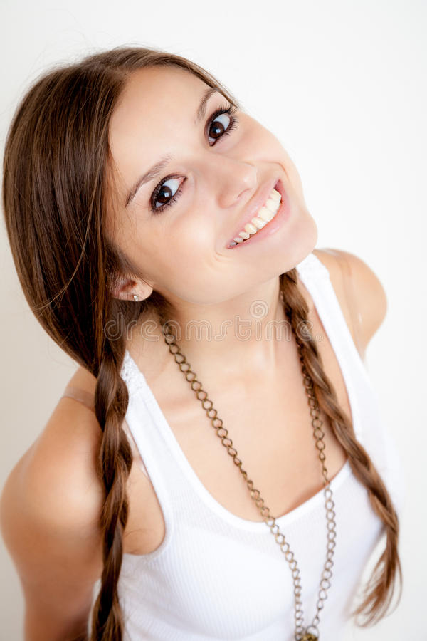 Smiling girl with braids. Looking at camera on white background royalty free stock photography
