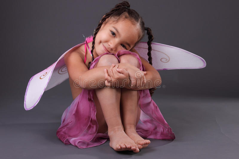 Smiling girl in butterfly wings. An isolated portrait of a happy girl in fairy wings royalty free stock images