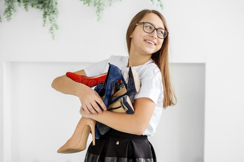 A smiling girl buys a lot of shoes. Discounts. Concept fashion, shopping, clothing, lifestyle, shopping center royalty free stock photos