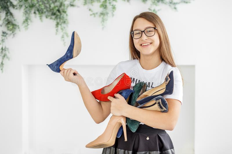 A smiling girl buys a lot of shoes. Sale. Concept fashion, shopping, clothing, lifestyle, shopping center royalty free stock photo