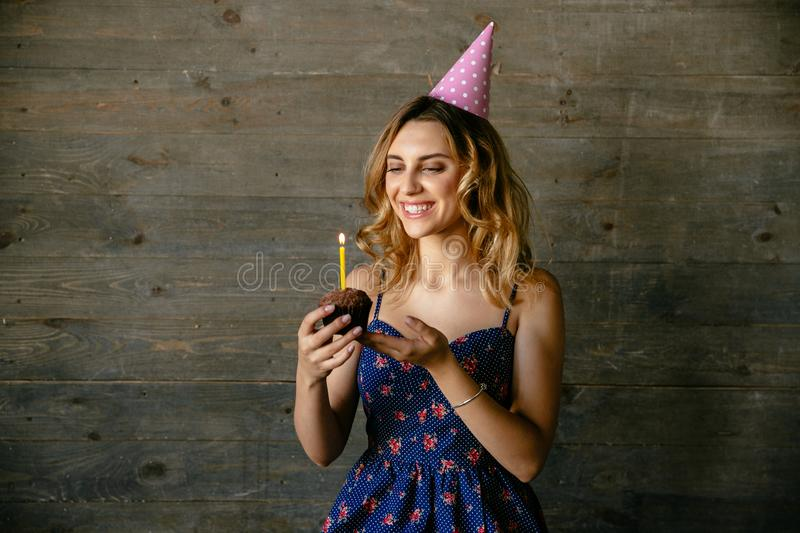 Smiling girl celebrating her birthday. Happy attractive girl looking at chocolate cupcake, celebrating own birthday. Dressed in blue dress, in festive hat royalty free stock images