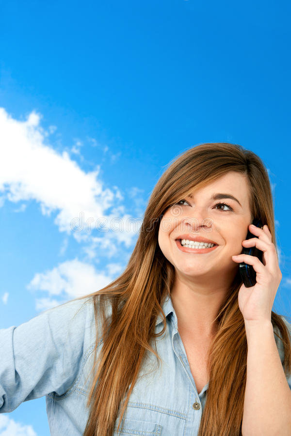 Smiling girl on cellphone outdoors. royalty free stock photos