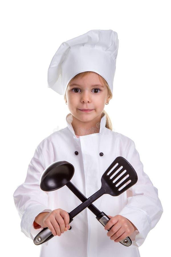 Smiling girl chef white uniform isolated on white background. Holding black ladle and scapula crossed. Portrait image royalty free stock photos