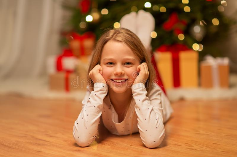 Smiling girl at christmas home. Christmas, holidays and childhood concept - smiling girl at home royalty free stock photos