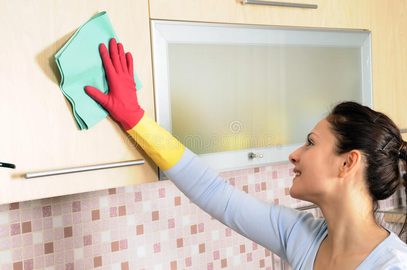 Smiling girl cleaning the house stock image