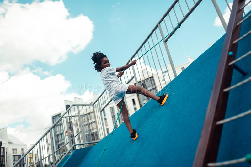 Smiling girl climbing up on a sports ground. Conquering a peak. Smiling school girl climbing up on a sports ground holding a rope stock image