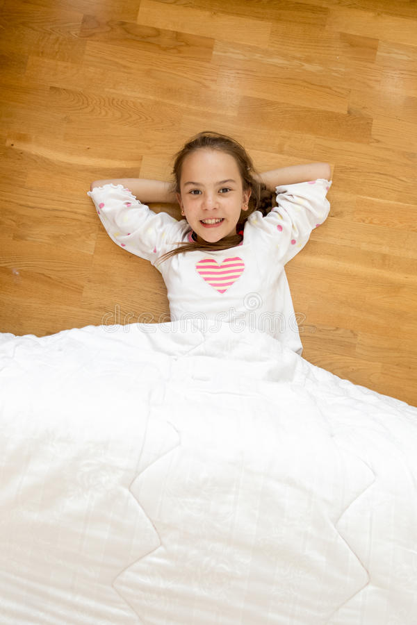 Smiling girl covered with blanket lying on wooden floor royalty free stock photo