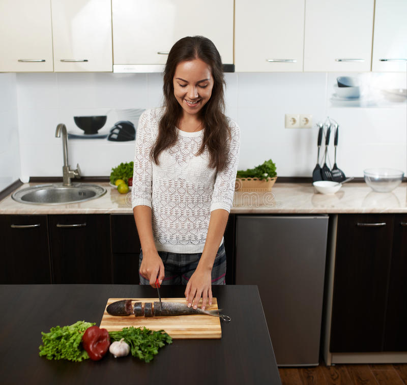 Smiling girl cut fish. To prepare dinner royalty free stock photos