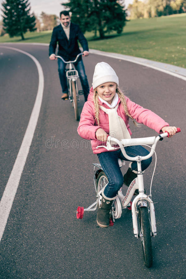 Smiling girl cycling with father stock photo