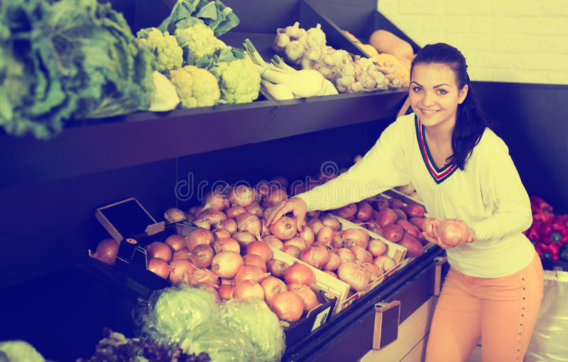 Smiling girl deciding on onions stock photography