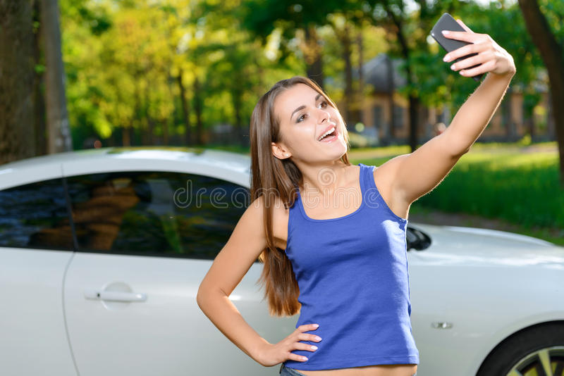 Smiling girl doing selfie on background of car royalty free stock images