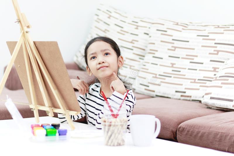 Smiling girl drawing a picture and dreaming at home.  royalty free stock images