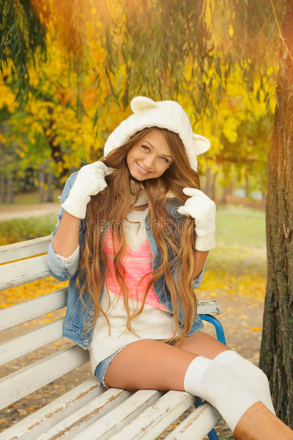 Smiling girl dressed in a cute knitted white bear hat in autumn park. royalty free stock images