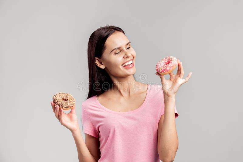 Smiling girl dressed in pink t-shirt holds two mouth-watering donuts in her hands on the white background in the studio stock photo