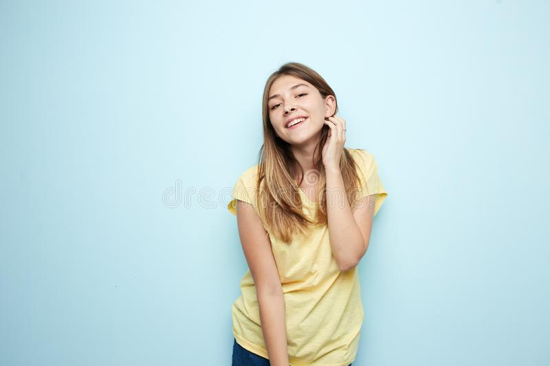 Smiling girl dressed in a yellow t-shirt and jeans is on a blue background in the studio stock photos