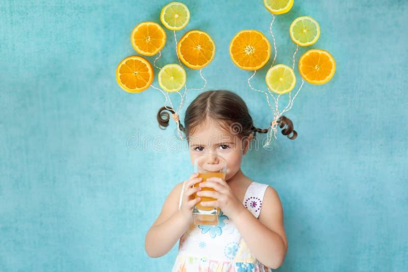 Smiling girl drinks fresh orange juice. Funny girl drinks fresh citrus juice with bright balloons orange and lemon slices on her pigtails royalty free stock images