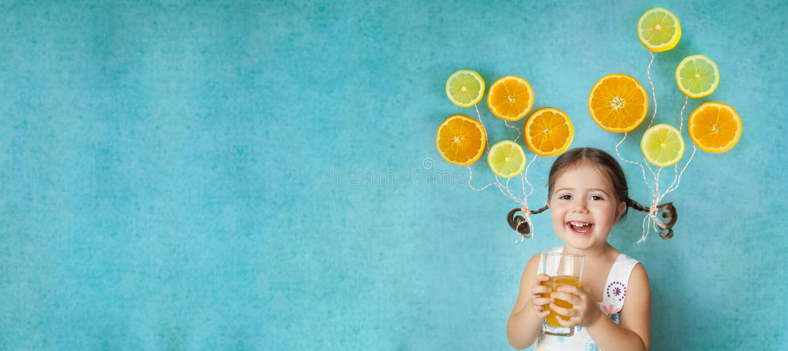 Smiling girl drinks fresh orange juice. Laughing girl keeps glass of fresh citrus juice with bright balloons orange and lemon slices on her pigtails. Healthy stock photo