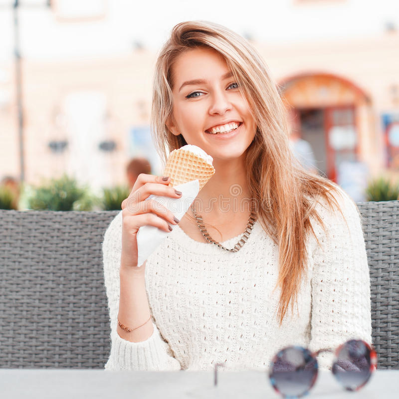 Smiling girl eating an ice-cream scoop in a waffle cone royalty free stock photography