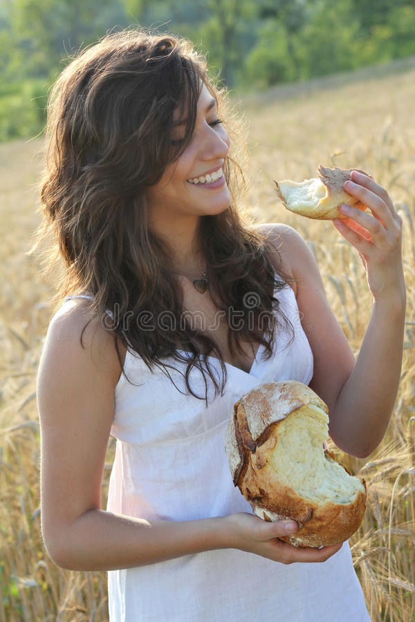 Smiling girl eats a piece of bread stock images