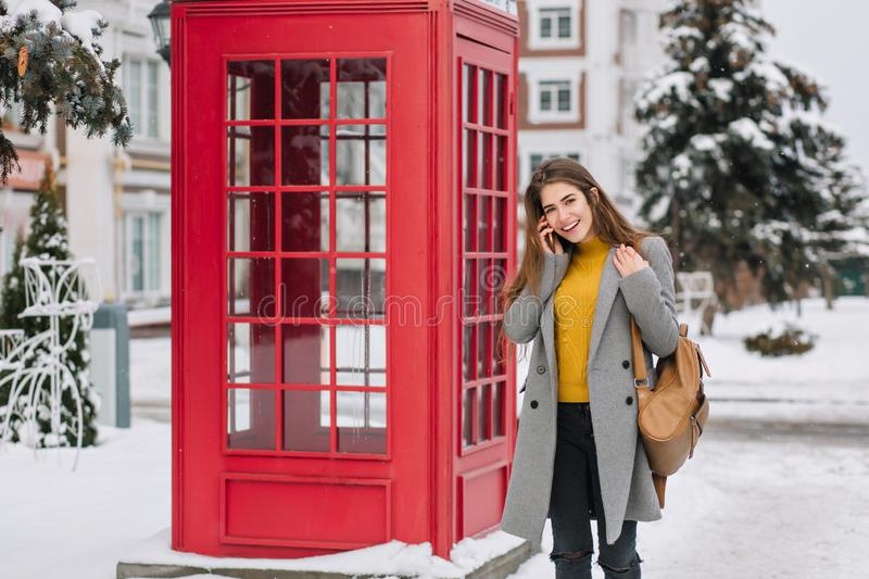 Smiling girl in elegant attire talking on smartphone while standing near british phone booth in winter. Outdoor photo of. Pleased brunette woman in trendy coat stock photo