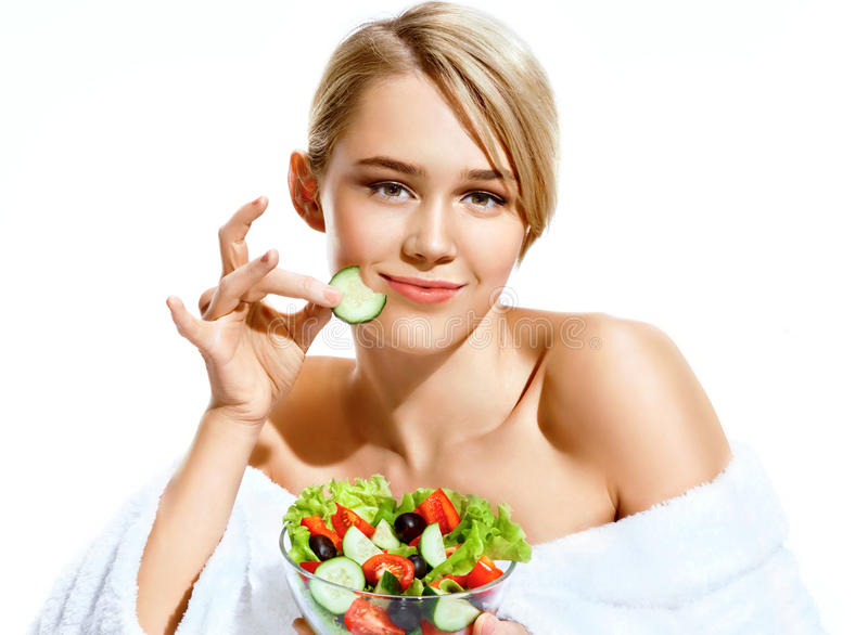 Smiling girl enjoying a fresh salad and bites a piece of cucumber royalty free stock photo