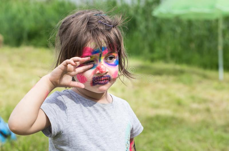 Smiling girl with face art painting like tiger, little boy making face painting, halloween party, child with funny face painting stock images