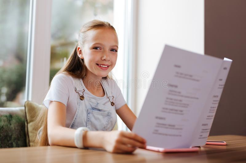 Smiling girl feeling cheerful while resting with parents in restaurant stock images